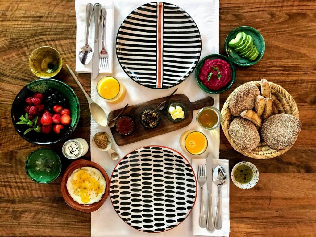 breakfast spread on a walnut table with orange juice, fresh berries, artisan bread, olive tapenade, fried egg, pink hummus, avocado
