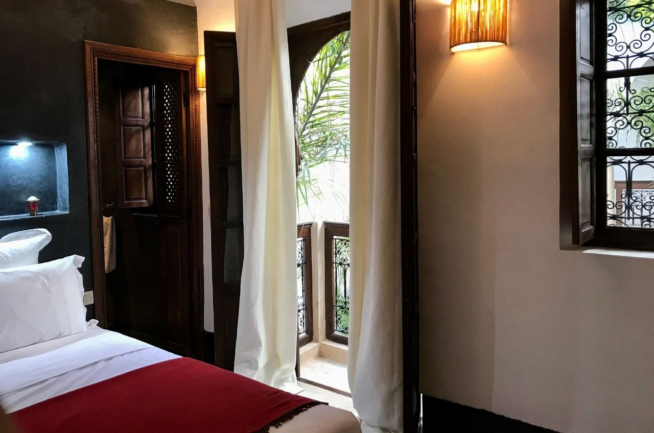 marrakech riad bedroom with double doors leading to balcony with view over courtyard